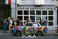 ******** Haus am Checkpoint Charlie (Check Point Charlie Museum). In the foreground a car painted with copies of the graffiti that were on the Berlin Wall
