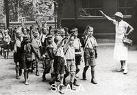 ******** A teacher is seeing off her school children with the 'Hitler Gruss' (Hitler greeting). Photography. Around 1933
